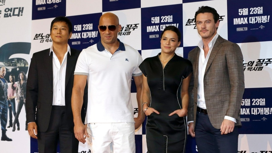 "Actors and actress, from left, Sung Kang, Vin Diesel, Michelle Rodriguez and Luke Evans pose for the media during a press conference to promote their new film ""Fast & Furious 6"" in Seoul, South Korea, Monday, May 13, 2013."