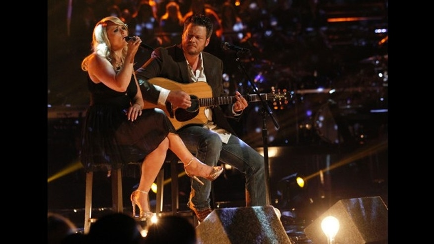 "This May 21, 2013 photo released by NBC shows married singers Miranda Lambert, left, and  Blake Shelton performing an acoustic version of the hit ""Over You"" during a broadcast of the singing competition series, ""The Voice,"" in Los Angeles."