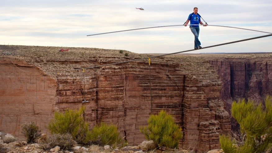 IMAGE DISTRIBUTED FOR DISCOVERY COMMUNICATIONS - Nik Wallenda nears the completion of his 1400 foot walk across the Grand Canyon for Discovery Channel's Skywire Live With Nik Wallenda on Sunday, June 23, 2013 at the Grand Canyon, Calif. (Tiffany Brown/AP Images for Discovery Communications)