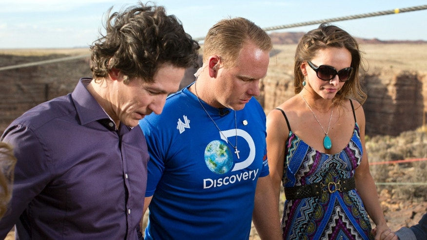 IMAGE DISTRIBUTED FOR DISCOVERY COMMUNICATIONS - Preacher Joel Osteen, left, leads prayer with Nik and Erendira Wallenda ahead of Nik's 1400 foot walk across the Grand Canyon for Discovery Channel's Skywire Live With Nik Wallenda on Sunday, June 23, 2013 at the Grand Canyon, Calif. (Tiffany Brown/AP Images for Discovery Communications)