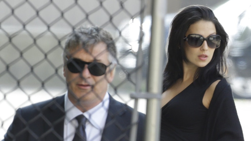 June 27, 2013: Alec Baldwin, left, and his wife Hilaria Thomas arrive at Cathedral Church of Saint John the Divine before funeral services actor James Gandolfini in New York.