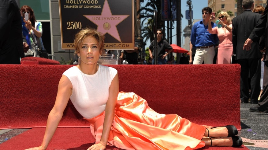 Jennifer Lopez poses with her new star on the Hollywood Walk of Fame on Thursday, June 20, 2013 in Los Angeles.