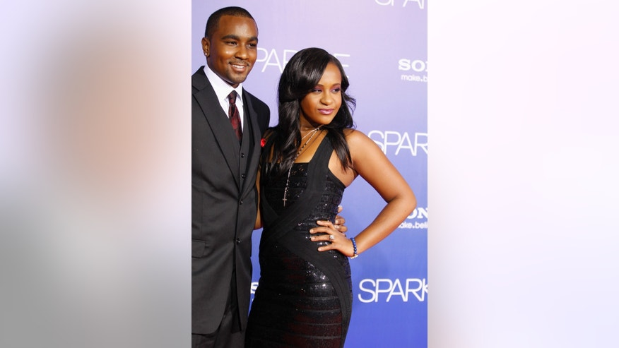 "Bobbi Kristina Brown, daughter of the late singer Whitney Houston, reveals a tattoo with the initials ""W H"" as she waves while arriving with boyfriend Nick Gordon at the premiere of the new film ""Sparkle"" starring Jordin Sparks and the late Whitney Houston in Hollywood August 16, 2012."