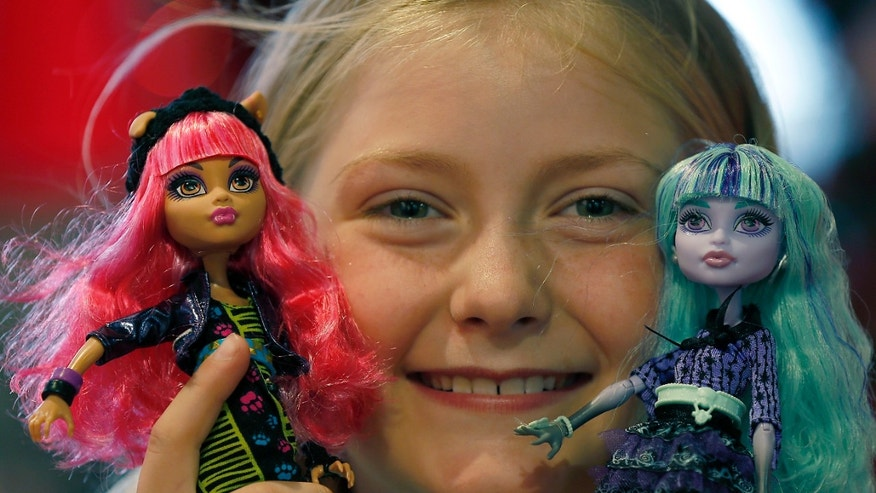 In this Thursday, June 27, 2013, photo,Tegan, 9, poses with Monster High Dolls as part of a Christmas toy preview at the toy store Hamleys in London. Mattels Monster High Dolls, with neon hair and punk clothing, have grown to an estimated $500 million in annual sales since debuting in 2010. (AP Photo/Frank Augstein)