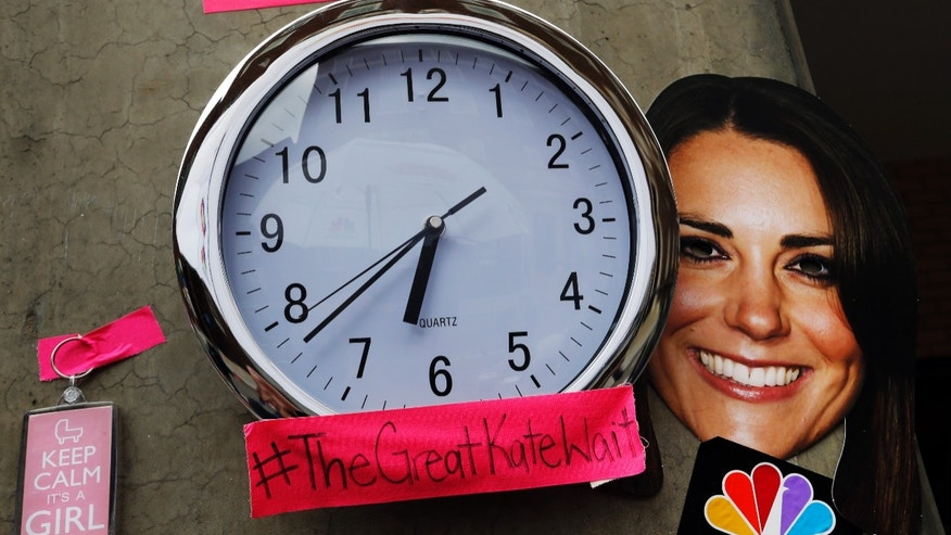 A mask depicting Britain's Duchess of Cambridge and a clock showing New York time, which were placed by members of the media, is seen across St. Mary's Hospital exclusive Lindo Wing in London, Sunday, July 21, 2013. Media are preparing for royal-mania as the Duchess is expected to give birth to the new third-in-line to the throne in mid-July, at the Lindo Wing. Cameras from all over the world are set to be jostling outside for an exclusive first glimpse of Britain's Prince William and the Duchess of Cambridge's first child. (AP Photo/Lefteris Pitarakis)