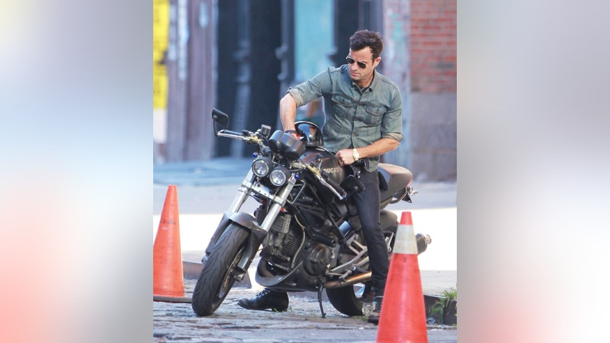 Justin Theroux puts his license place back on his Ducati with Velcro and rides off in NYC.