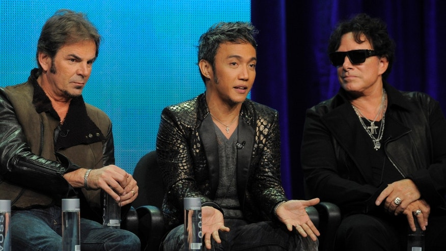 "Jonathan Cain, left, Arnel Pineda, center, and Neal Schon of the rock band Journey take part in a panel discussion on the Independent Lens documentary ""Don't Stop Believin': Everyman's Journey,"" at the PBS Summer 2013 TCA press tour at the Beverly Hilton Hotel on Tuesday, Aug. 6, 2013, in Beverly Hills, Calif. (Photo by Chris Pizzello/Invision/AP)"