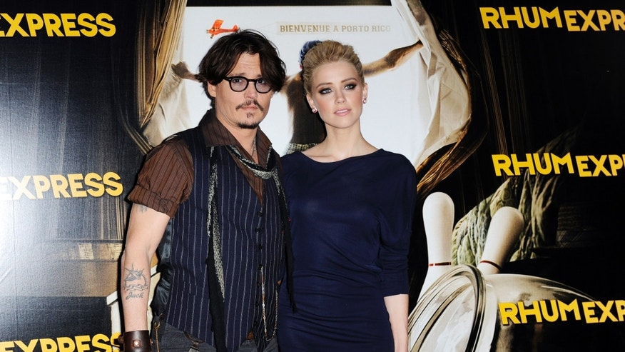 "Johnny Depp and Amber Heard pose for photographers as they arrive for the premiere of the film ""The Rum Diary"" in Paris November 8, 2011"