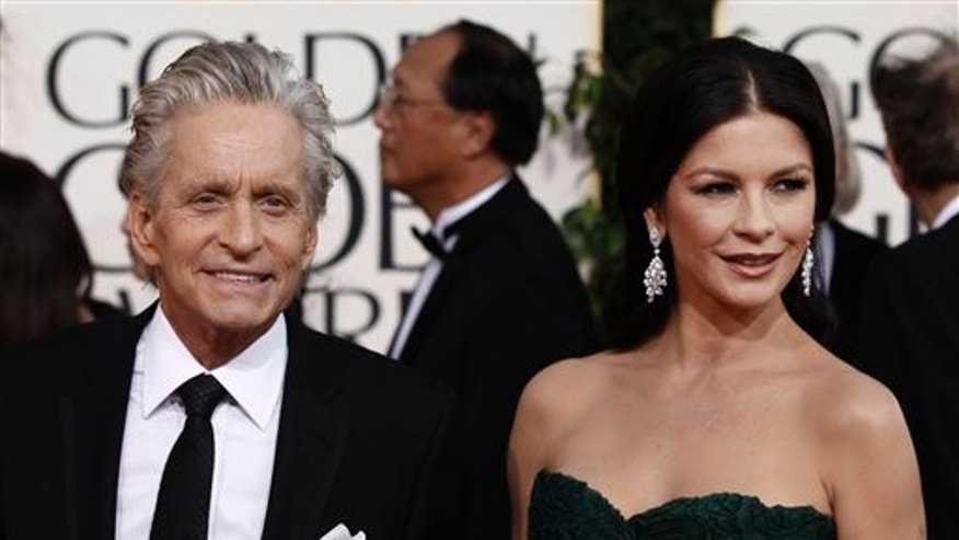 Michael Douglas arrives with his wife Catherine Zeta-Jones for the Golden Globe Awards Sunday, Jan. 16, 2011, in Beverly Hills, Calif. (AP Photo/Matt Sayles)