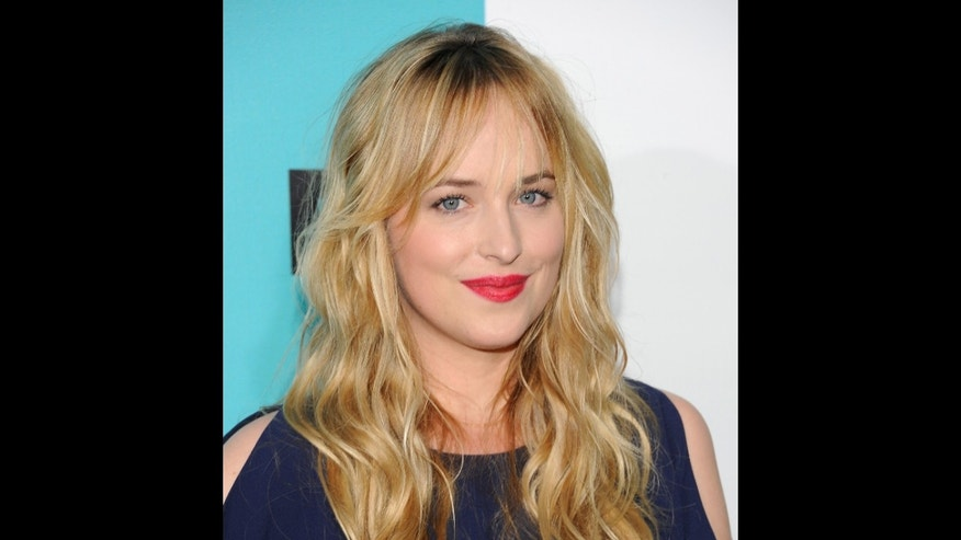 FILE - Dakota Johnson attends the FOX network upfront presentation party at Wollman Rink, in New York in a May 14, 2012 file photo. Focus Features and Universal Pictures announced Monday, Sept. 2, 2013 that Dakota Johnson will play Anastasia Steele in the big-screen adaptation of E L James Fifty Shades of Grey. Johnson is the daughter of actors Don Johnson and Melanie Griffith. (AP Photo/Evan Agostini, File)