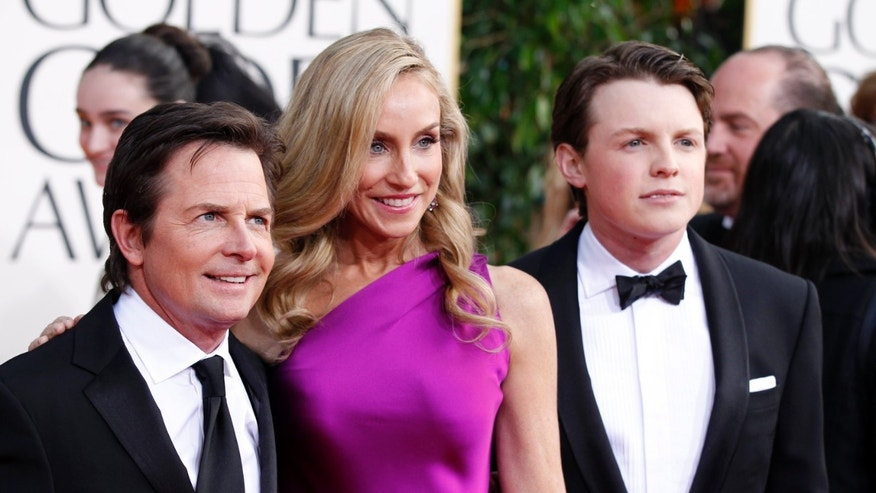 Actor Michael J. Fox, his wife Tracy Pollan and their son Sam Fox (R) arrive at the 70th annual Golden Globe Awards in Beverly Hills, California, January 13, 2013.