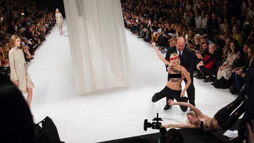 Two Femen activists shout slogans and rush through the runway to disturb the presentation of Nina Ricci's ready-to-wear Spring/Summer 2014 fashion collection Thursday, Sept. 26, 2013 in Paris.