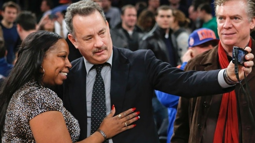 Actor Tom Hanks (C) tries to take a picture with a fan after the New York Knicks played the Los Angeles Clippers in their NBA basketball game at Madison Square Garden in New York, February 10, 2013. Actor Christopher McDonald (R) watches. REUTERS/Ray Stubblebine  (UNITED STATES - Tags: SPORT BASKETBALL) - RTR3DLLE