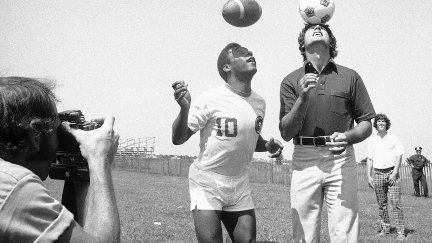 In this Aug. 5, 1975, file photo, New York Jets quarterback Joe Namath bounces a soccer ball on his head while Pele uses his head to get a feel for the pigskin at the Jets' training camp in Hempstead, N.Y.