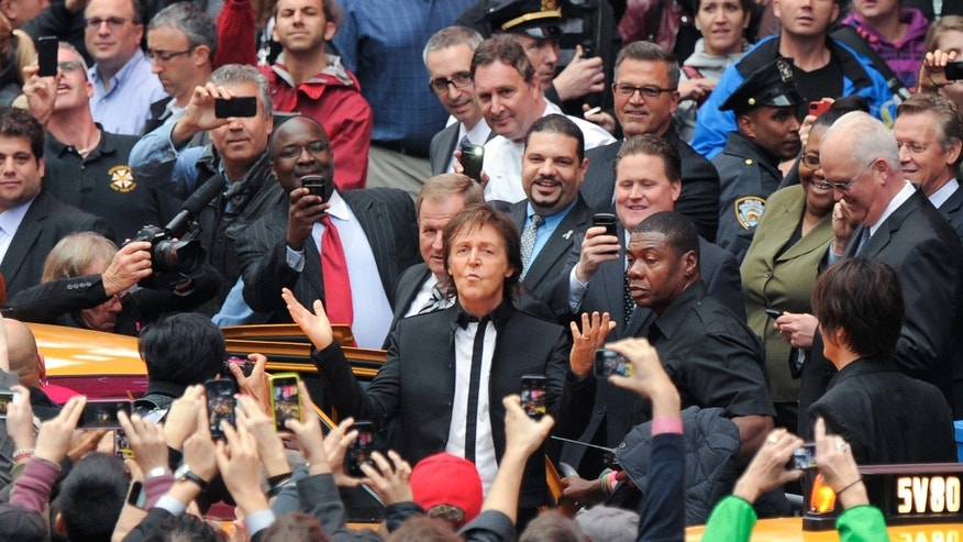 "Paul McCartney arrives with his band to give a surprise pop up concert in Times Square on Thursday, Oct. 10, 2013 in New York. McCartney will release his new album called ""New"" on October 15. (Photo by Evan Agostini/Invision/AP)"