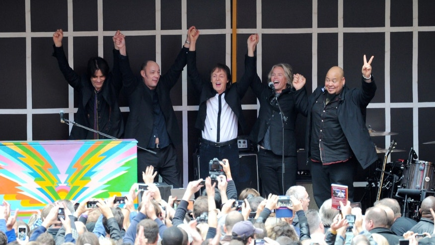 "Paul McCartney and his band give a surprise pop up concert in Times Square on Thursday, Oct. 10, 2013 in New York. McCartney will release his new album called ""New"" on October 15. (Photo by Evan Agostini/Invision/AP)"
