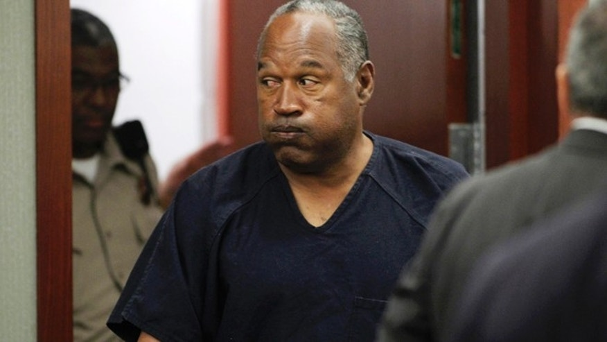 O.J. Simpson returns to the courtroom after a lunch break during the fifth day of an evidentiary hearing in Clark County District Court in Las Vegas, Nevada  May 17, 2013. Simpson, who is currently serving a nine-to-33-year sentence in state prison as a result of his October 2008 conviction for armed robbery and kidnapping charges, is using a writ of habeas corpus to seek a new trial, claiming he had such bad representation that his conviction should be reversed.  REUTERS/Steve Marcus (UNITED STATES  - Tags: CRIME LAW SPORT ENTERTAINMENT)   - RTXZR2N