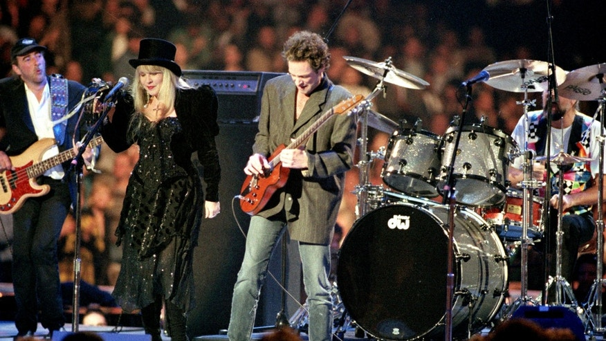 In a Monday, Jan. 18, 1993 file photo, the rock group Fleetwood Mac, reuniting after 13 years apart, performs during the American Gala evening at the Capital Centre in Landover, Md.   From left to right are, John McVie, Stevie Nicks, Lindsey Buckingham and Mick Fleetwood. Fleetwood Mac annunced Sunday, Oct. 27, 2013 that the group is canceling planned performances in Australia and New Zealand as bassist John McVie is treated for cancer.
