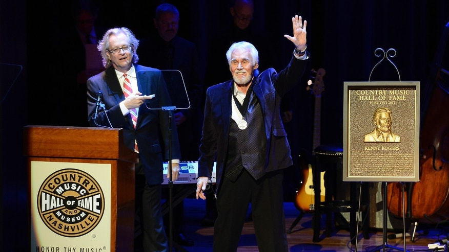 "Country music star Kenny Rogers thanks the audience at the ceremony for the 2013 inductions into the Country Music Hall of Fame on Sunday, Oct. 27, 2013, in Nashville, Tenn. The inductees are Bobby Bare, the late ""Cowboy"" Jack Clement and Kenny Rogers. (AP Photo/Mark Zaleski)"