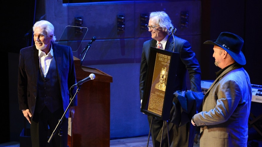 "Country music star Kenny Rogers is presented a plaque as country music singer Garth Brooks, right, look on at the ceremony for the 2013 inductions into the Country Music Hall of Fame on Sunday, Oct. 27, 2013, in Nashville, Tenn. The inductees are Bobby Bare, the late ""Cowboy"" Jack Clement and Kenny Rogers. (AP Photo/Mark Zaleski)"