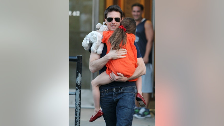 "This Tuesday July 17, 2012 photo shows actor Tom Cruise and daughter Suri Cruise leaving Chelsea Piers in New York.  Cruise wrote in a sworn declaration filed Tuesday Nov. 5, 2013, in a defamation lawsuit against Bauer Publishing Co. that he maintains a close relationship with his daughter Suri despite the claims by two Bauer tabloids in 2012 that he had ""abandoned"" her. (AP Photo/ Donald Traill)"