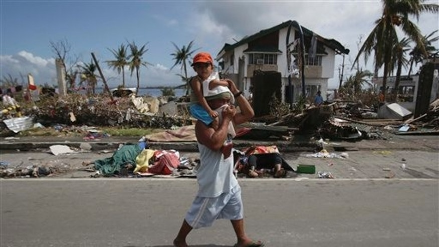 A man, holding a boy,  walks past dead bodies along the streets in typhoon-ravaged Tacloban city, Leyte province central Philippines on Monday, Nov. 11, 2013.  Typhoon-ravaged Philippine islands faced an unimaginably huge relief effort that had barely begun Monday, as bloated bodies lay uncollected and uncounted in the streets and survivors pleaded for food, water and medicine. (AP Photo/Aaron Favila)