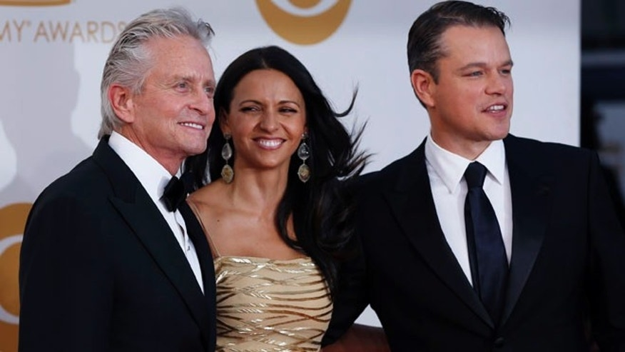 "Actor Michael Douglas from HBO's movie ""Behind the Candelabra"" arrives with co-star Matt Damon and his wife, Luciana Barroso, at the 65th Primetime Emmy Awards in Los Angeles September 22, 2013. REUTERS/Mario Anzuoni (UNITED STATES Tags: ENTERTAINMENT) (EMMYS-ARRIVALS) - RTX13VT2"