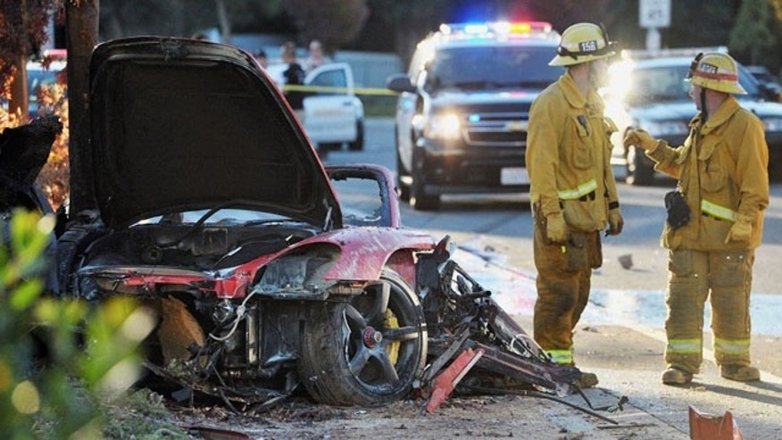 "November 30, 2013: Sheriff's deputies work near the wreckage of a Porsche that crashed into a light pole on Hercules Street near Kelly Johnson Parkway in Valencia, Calif. A publicist for actor Paul Walker says the star of the ""Fast & Furious"" movie series died in the crash north of Los Angeles. He was 40. (AP Photo/The Santa Clarita Valley Signal, Dan Watson)"