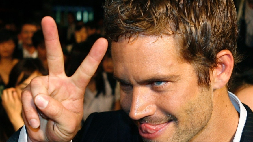 "April 15, 2009. Paul Walker gestures to a fan during the premiere of the movie ""Fast and Furious 4"" in Taipei."