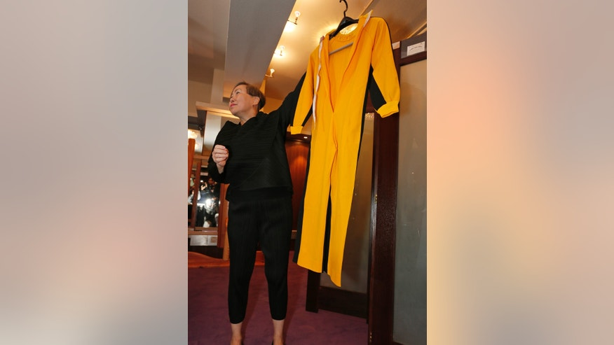 Anna Lee, vice-chairman of Spink auction house, holds Bruce Lees original yellow jumpsuit he wore in Game of Death during an auction preview in Hong Kong, Monday, Dec. 2, 2013. Its part of a collection of 14 items including clothing and props going on the block on Thursday. Lee died in 1973, before the movie was finished. Spink estimates the suit will fetch 250,000 to 300,000 Hong Kong dollars ($32,250-$38,700). (AP Photo/Vincent Yu)