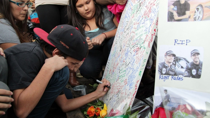 VALENCIA, CA - DECEMBER 01:  Fans pay tribute to actor Paul Walker at the site of his fatal car accident on December 1, 2013 in Valencia, California.  Walker died on November 30, 2013 at age 40. (Photo by David Buchan/Getty Images)
