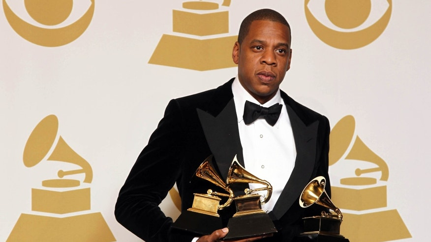 "Jay-Z poses backstage with the awards for best rap/sung collaboration for ""No Church in the Wild"" and best rap performance for ""N****s in Paris"" at the 55th annual Grammy Awards on Sunday, Feb. 10, 2013, in Los Angeles."