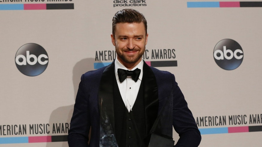 November 24, 2013. Musician Justin Timberlake poses backstage with his awards at the 41st American Music Awards in Los Angeles, California.