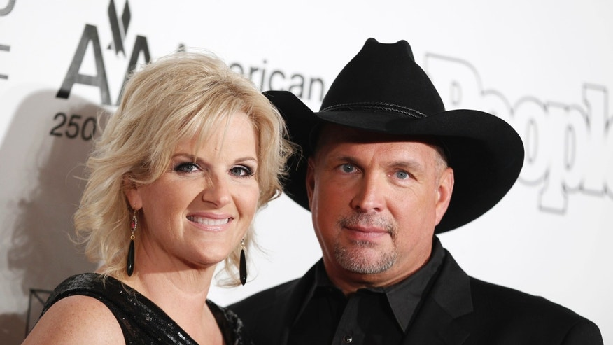 Singers Garth Brooks (R) and Trisha Yearwood pose as they arrive for the Songwriters Hall of Fame awards in New York June 16, 2011.  REUTERS/Lucas Jackson (UNITED STATES - Tags: ENTERTAINMENT) - RTR2NR8A