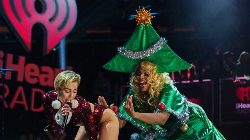 December 13, 2013. Singer Miley Cyrus twerks a performer dressed as a Christmas tree as she performs during the 2013 Z100 Jingle Ball in New York.
