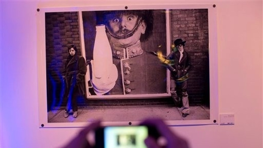 A visitor takes a picture of a 1968 Michael Cooper photo of Rolling Stones frontman Mick Jagger and guitarist Keith Richards, on the eve of the inauguration of Stones 50, an exhibit of Cooper's photos, the official photographer of the Rolling Stones in the first years of the band, presented by his son Adam, at the Centro Cultural Borges in Buenos Aires, Argentina, Thursday, Dec. 12, 2013. (AP Photo/Rodrigo Abd)