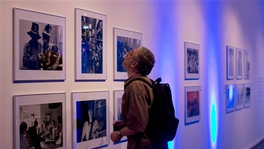 A journalist reviews Michael Cooper photos of the Rolling Stones, on the eve of the inauguration of Stones 50, an exhibit of Cooper's photos, the official photographer of the Rolling Stones in the first years of the band, presented by his son Adam, at the Centro Cultural Borges in Buenos Aires, Argentina, Thursday, Dec. 12, 2013. (AP Photo/Rodrigo Abd)
