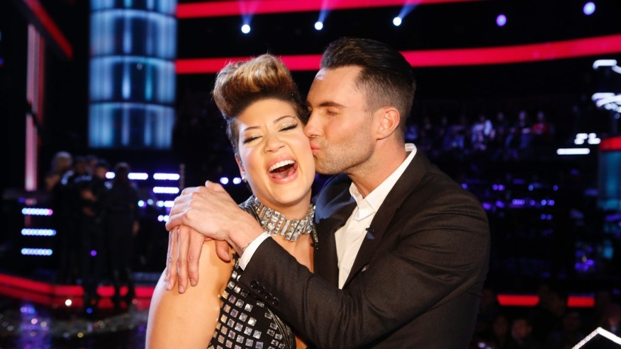 "In this photo provided by NBC, Maroon 5 frontman Adam Levine, right, kisses Tessanne Chin on the cheek after Chin was announced the season five winner of ""The Voice"" on Tuesday, Dec. 17, 2013, in Los Angeles. Chin a 28-year-old Kingston native had nearly given up on her dreams before landing a spot on the NBC singing competition. Levine was Chin's coach. (AP Photo/NBC,Trae Patton)"