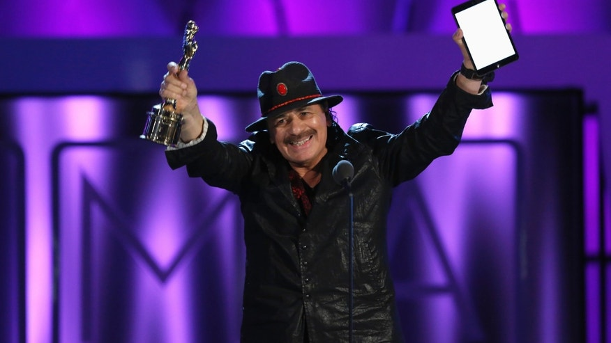 Musician Carlos Santana accepts the Outstanding Commitment to Cause and Community Award at the 2013 NCLR ALMA Awards at the Pasadena Civic Auditorium in Pasadena, California September 27, 2013.