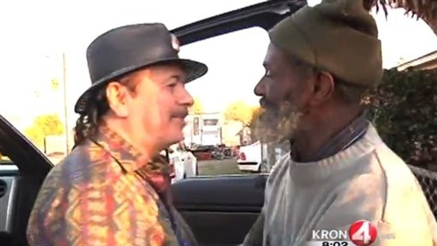 "In this Friday, Dec. 20, 2013 frame grab from video provided by KRON-TV, famed rock guitarist Carlos Santana, left, greets his former bandmate Marcus Malone on the streets of Oakland, Calif.  It had been decades since Santana had seen Malone, who now describes himself as homeless and living on the streets of Oakland. KRON-TV reporter Stanley Roberts ran into percussionist Marcus ""The Magnificent"" Malone while working on a story about illegal dumping. Although he initially was skeptical of the homeless man's claim that the Santana Blues Band got its start in his mother's garage in the late 1960s, Roberts checked out the story and confirmed it. And on Friday, he took Santana for a surprise visit to the camper where Malone has been staying. (AP Photo/KRON-TV)"