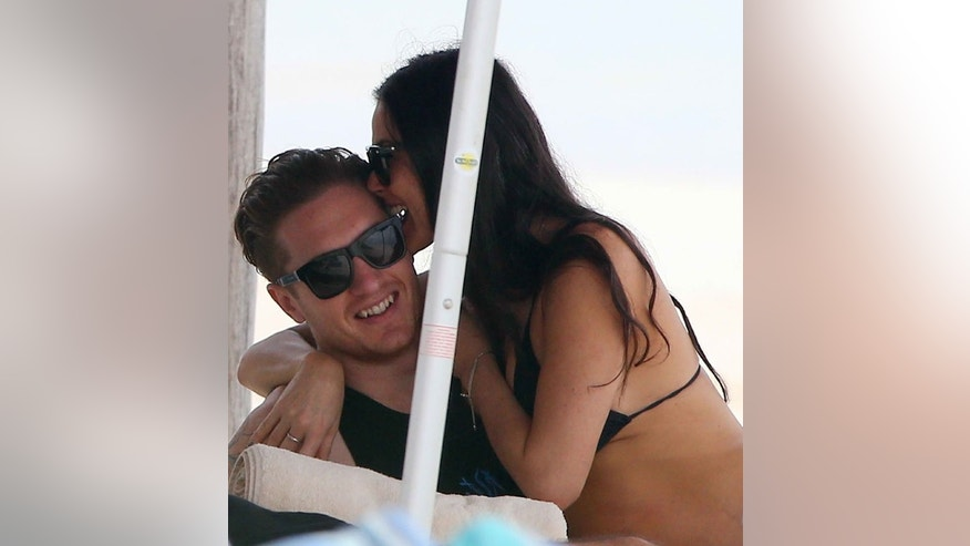 Demi Moore gets close to an unidentified male companion.