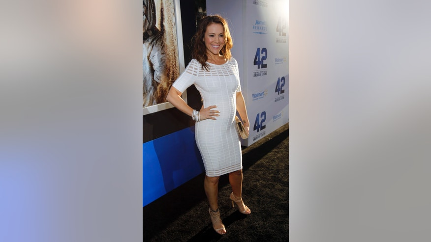 "April 12, 2013. Actress Alyssa Milano poses at the premiere of ""42"" in Hollywood, California."