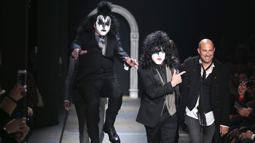 January 11, 2014. American fashion designer John Varvatos, right, is accompanied by Rock Band Kiss as he acknowledges the applause of the audience, at the end of his men's Autumn-Winter 2014 collection, part of the Milan Fashion Week, unveiled in Milan, Italy.