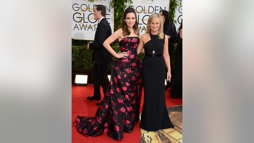 Tina Fey, left, and Amy Poehler arrive at the 71st annual Golden Globe Awards at the Beverly Hilton Hotel on Sunday, Jan. 12, 2014, in Beverly Hills, Calif. (Photo by Jordan Strauss/Invision/AP)
