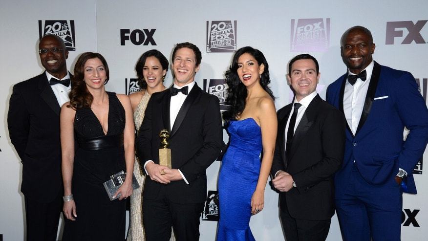 "Andy Samberg (4th L) poses with cast members (L-R) Andre Braugher, Chelsea Peretti, Melissa Fumero, Stephanie Beatriz, Joe Lo Truglio and Terry Crews with their Golden Globe for ""Brooklyn Nine-Nine"" at the Fox Golden Globe party in Beverly Hills, California January 12, 2014. REUTERS/Phil McCarten (UNITED STATES) (GOLDENGLOBES-PARTIES) - RTX17C17"