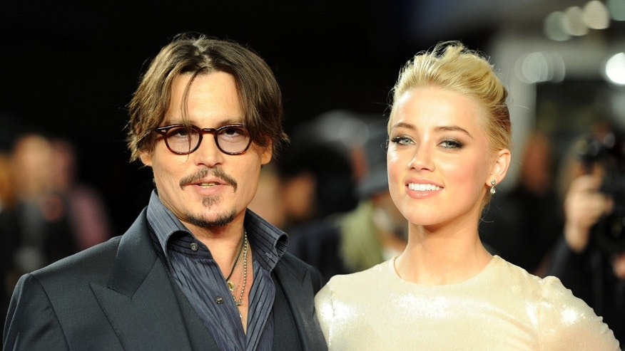 "November 3, 2011. Johnny Depp and Amber Heard pose for photographers as they arrive for the European premiere of ""The Rum Diary"" in London."