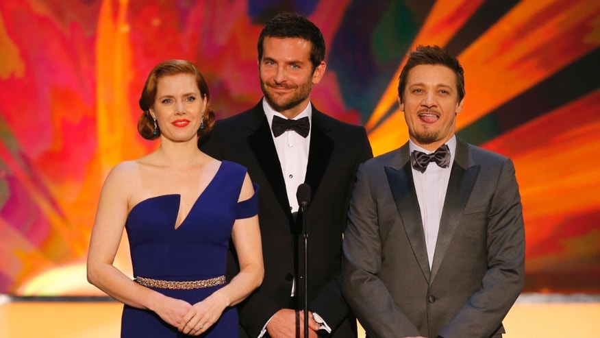 "January 18, 2014. Amy Adams, Bradley Cooper (C) and Jeremy Renner introduce a clip from the film ""American Hustle"" at the 20th annual Screen Actors Guild Awards in Los Angeles, California."