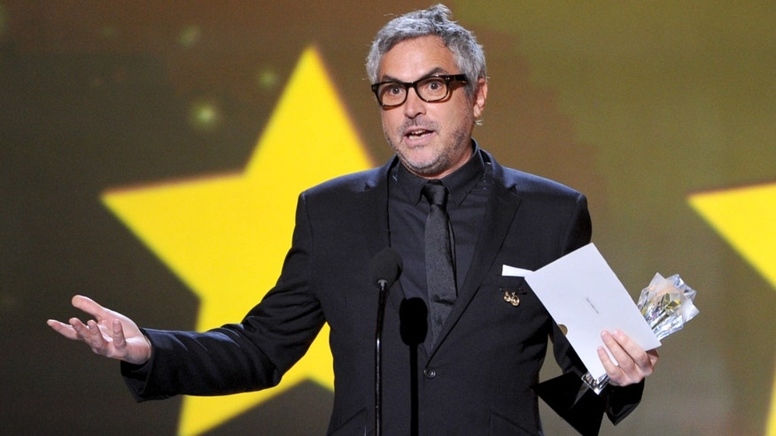 "SANTA MONICA, CA - JANUARY 16:  Director Alfonso Cuarón accepts the Best Director award for ""Gravity"" onstage during the 19th Annual Critics' Choice Movie Awards at Barker Hangar on January 16, 2014 in Santa Monica, California.  (Photo by Kevin Winter/Getty Images)"