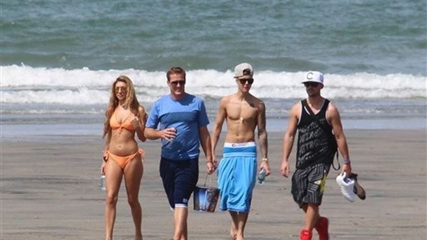 Justin Bieber, second right, and Chantel Jeffries, far left, walk with unidentified people on a beach in Punta Chame, Panama, Saturday, Jan. 25, 2014.