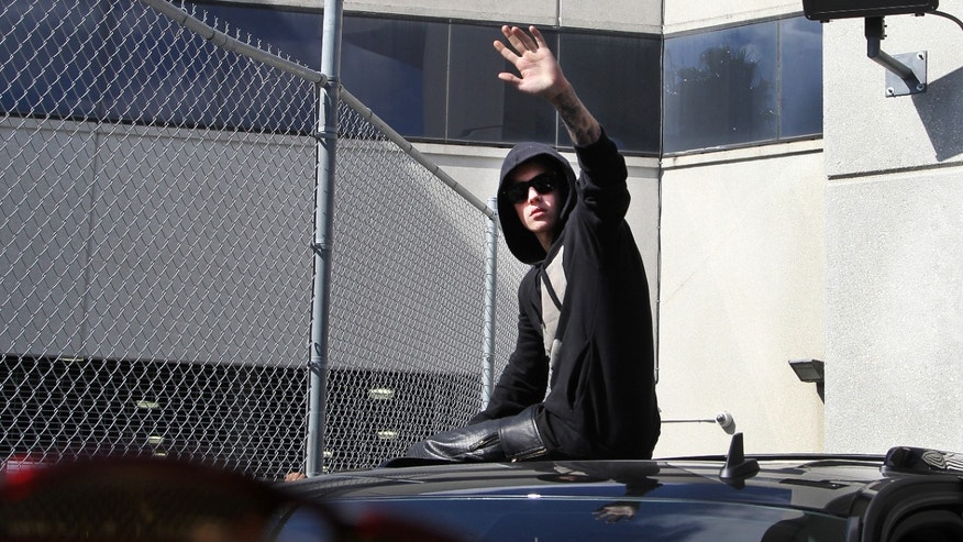 FILE - In this Thursday, Jan. 23, 2014 file photo, singer Justin Bieber waves from atop an SUV as he leaves the Turner Guilford Knight Correctional Center, in Miami. Bieber was released from jail following his arrest on charges of driving under the influence, driving with an expired license and resisting arrest. Bieber's court cases on both sides of the U.S.-Canadian border might not just lead to more scrutiny by judges and prosecutors, but could also complicate the pop star's jet-setting ways. (AP Photo/El Nuevo Herald, Hector Gabino, file) FLORIDA KEYS OUT, MAGS OUT, NO SALES. DIARIO LAS AMERICAS OUT